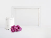 White blank wooden frame mockup with old tin and pink rose flowers lying on the table. Poster product design. Styled. White blank wooden frame mockup with old Stock Image