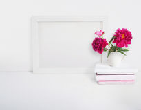 White blank wooden frame mockup with a peony flowers bouquet in a porcelain cup and pile of books lying on the table Royalty Free Stock Photo