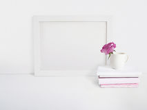 White blank wooden frame mockup with a rose flower in a porcelain cup and pile of books lying on the table. Poster Stock Photo