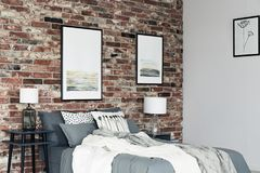 Paintings in cozy bedroom. White blanket on grey bed in cozy bedroom with paintings on brick wall and lamps on nightstands Royalty Free Stock Images