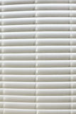 White Blinds. Detailed picture of closed white blinds blocking the sunlight Royalty Free Stock Photos