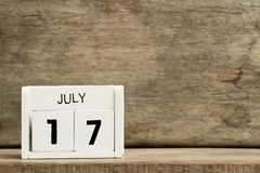 White block calendar present date 17 and month July. On wood background royalty free stock photography
