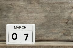 White block calendar present date 7 and month March. On wood background stock photo