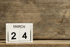 White block calendar present date 24 and month March. On wood background stock photography