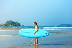 White blonde surfer girl holding surfboard goes to sea stock images