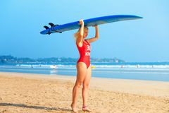 White blonde surfer girl in red swimsuit holding blue surfboard on the head royalty free stock image