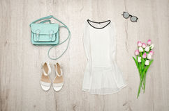 White blouse, glasses, white shoes, handbag and a bouquet of tulips. Fashionable concept. Wooden background Stock Photos