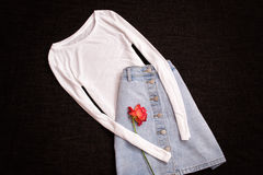 White blouse and jeans skirt, rose. Fashionable concept, top view Royalty Free Stock Photos