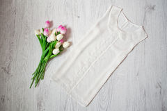 White blouse with lace, pink tulips. Fashionable concept, top view.  Royalty Free Stock Image