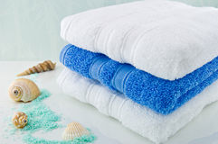White and Blue bath towels. Three folded towels, sea shells, and bath salts Stock Photos