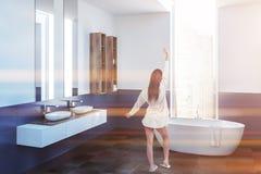White and blue bathroom corner, white tub, girl. Woman in a modern bathroom corner with white and blue walls, a tiled floor, a white bathtub standing under the stock photos