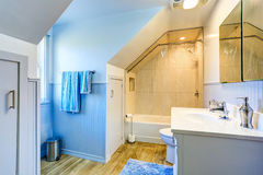 White and blue bathroom with shower and vaulted ceiling Stock Image