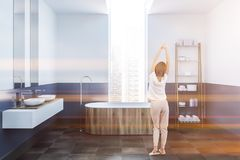 White and blue bathroom, wooden tub, woman. Woman in a modern bathroom interior with white and blue walls, a tiled floor, a wooden bathtub standing under the royalty free stock image