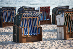White and blue beach chairs on the sand. White and blue beach chairs on the sand in the morning during summer, Ustka, Baltic Sea, Poland Royalty Free Stock Photography