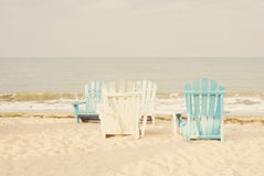 White and blue beach chairs on sand seascape and bright sky in summer vacation relax. Vintage filter tinting, sun haze, glare Royalty Free Stock Photos