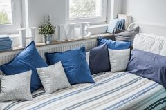 White and blue bedding set. On the bed Royalty Free Stock Photography