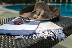 A white, blue and beige Turkish towel, sunglasses and straw hat on rattan lounger with blue swimming pool as background. Royalty Free Stock Image