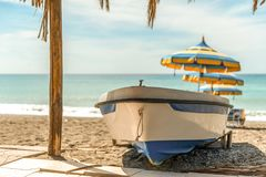 White blue boat on the beach. In the background you can see beach umbrellas and a calm Mediterranean sea Royalty Free Stock Photos