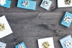 White and blue boxes are spread out in a circle on a brown wooden background. Gifts decorated with gold and silver bows stock photography