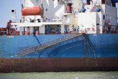 White blue brown Iron Ore Carrier. With ship gangway parked at a harbour Royalty Free Stock Photography
