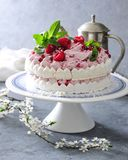 Meringue layer cake with fresh raspberry cream. On white and blue cake stand there is a ready to eat meringue layer cake with fresh raspberry cream. Decoreted Royalty Free Stock Image