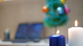 White and blue candles are burning in office at work place with Christmas tree background stock footage