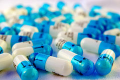 White and blue capsules. About 50 white and blue medication capsules spread on a white surface royalty free stock images