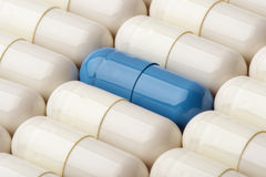 White and blue capsules of vitamins as background- macro. Royalty Free Stock Image