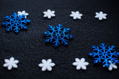White and blue Christmas snowflakes decoration on black textured background. White and blue Christmas snowflakes decoration on black textured background close Stock Images