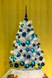 White blue Christmas tree. White sprig with blue balls with yellow background. Christmas tree with blue decoration Stock Photos
