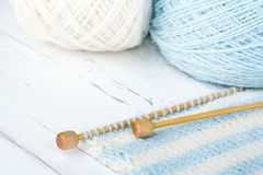 White and blue colored knitting on wooden background Royalty Free Stock Images
