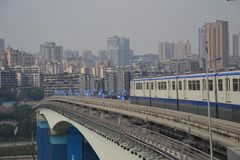Commuter Train in Chongquin, China. This is a white and blue commuter train in Chongquin, China crossing a transit bridge with blue accents with the skyline royalty free stock photo