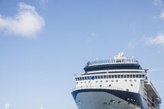 White and Blue Cruise Ship Under Puffy Clouds. Bow of blue and white luxury cruise ship under blue skies Stock Images