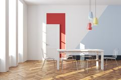 White and blue dining room. Modern dining room interior with whtie and blue walls, a white and red door, a wooden floor and a white table with transparent chairs Royalty Free Stock Image