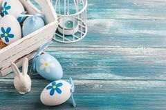 White blue easter eggs, bunny. And lit candle on wooden background Stock Image