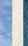 White and blue facade of modern building against blue sky backgr Stock Image