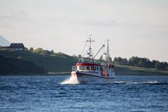 White and red fishing boat on the sea. Fjord in Norway royalty free stock images
