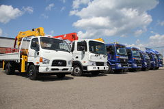White, blue flatbed trucks with crane arm is in the parking lot - Russia, Moscow, 30 August 2016 Royalty Free Stock Photos