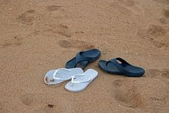WHITE AND BLUE FLIPFLOPS ON THE BEACH Royalty Free Stock Photos