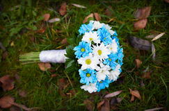 White and blue flowers. wedding bouquet. Lying on green grass Royalty Free Stock Photos