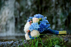 White and blue flowers wedding bouquet on a waterfall background. The White and blue flowers wedding bouquet on a waterfall background Royalty Free Stock Photography