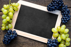 White and blue grapes and a slate with copyspace Royalty Free Stock Photo