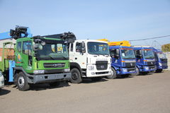 White, blue, green flatbed trucks with crane arm is in the parking lot - Russia, Moscow, 30 August 2016 Stock Photos