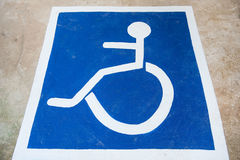 White and blue Handicap symbol car parking of disabled on the floor.  Royalty Free Stock Images
