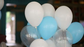 White and blue helium baloons. On the background of dark room stock video