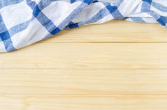 White and blue napkin on wooden table Royalty Free Stock Images