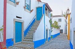 White and blue Obidos. The white houses of Obidos are decorated with bright blue or yellow stripes according to the old beliefs, Portugal Stock Photo