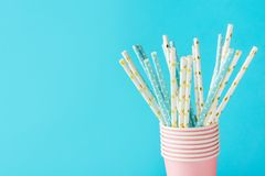White and blue paper drinking straws with golden star polka dot pattern in stacked pink cups. Zero waste nature friendly royalty free stock images