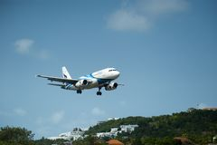 White and Blue Passenger Plane Passing Above Green Tree Covered Hill Royalty Free Stock Images