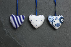 White Blue pattern Love Valentine's hearts hanging on grey slate Stock Photos
